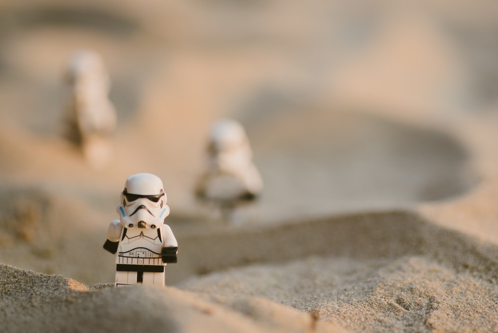 white lego minifig on brown sand