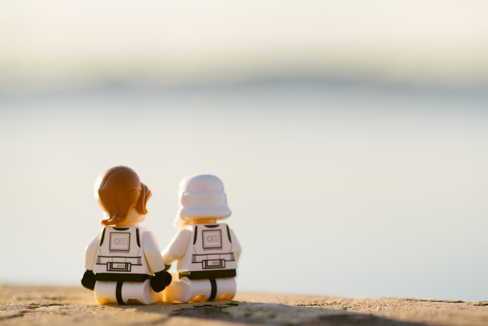 two lego toys on sand