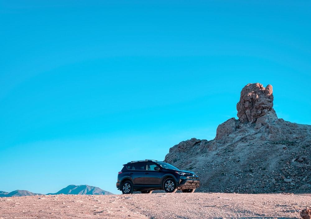 black suv on brown sand under blue sky during daytime