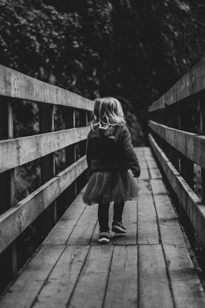 grayscale photo of woman walking on wooden bridge