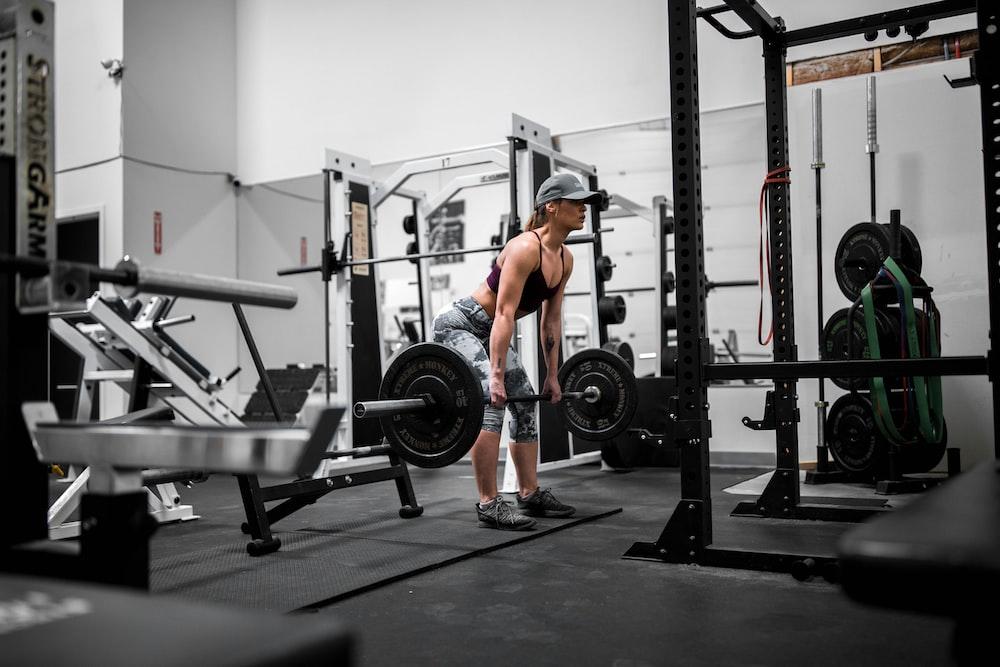 オレンジ色のタンクトップと黒のショートパンツで運動をしている男