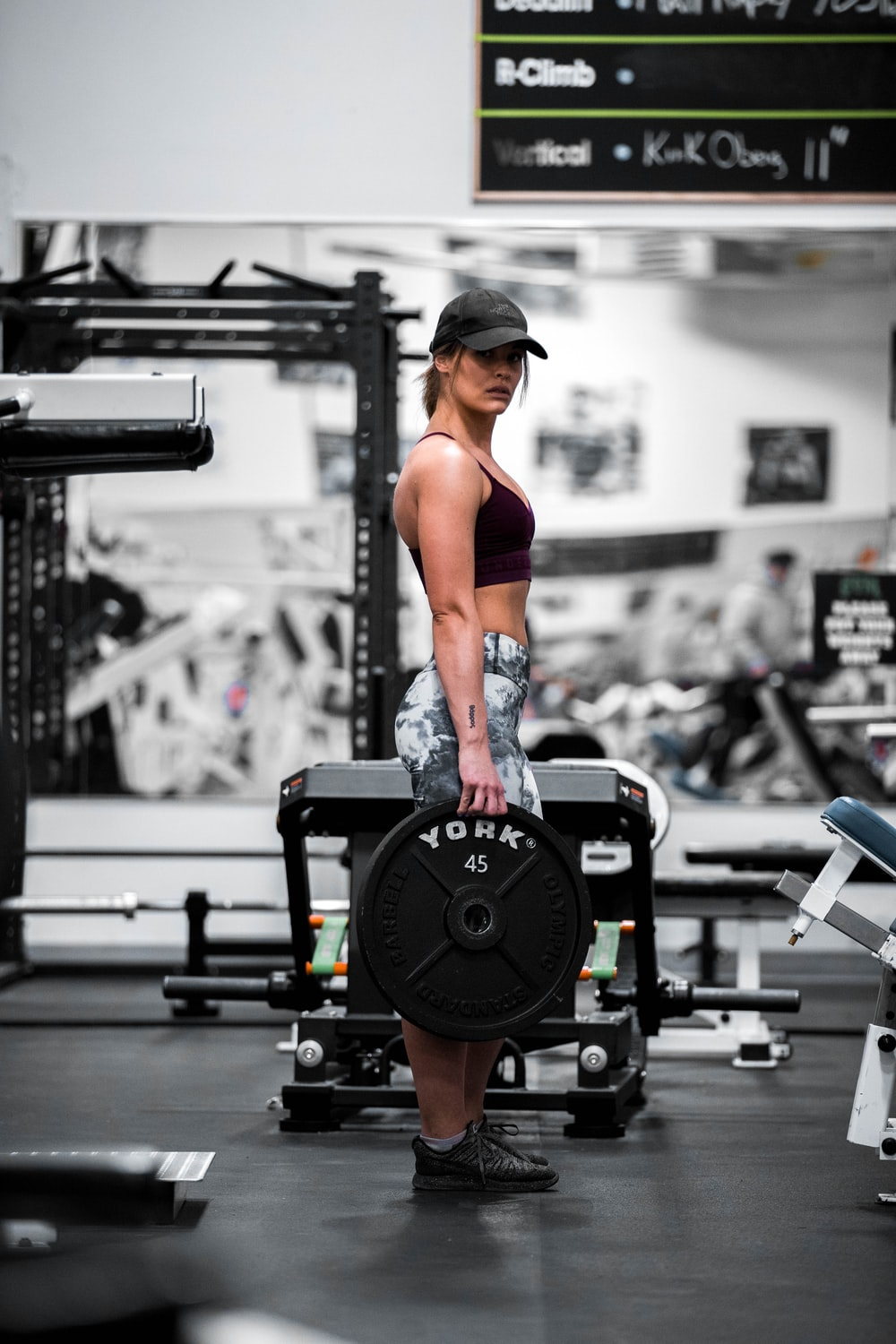 woman in red sports bra and black and gray shorts exercising on black exercise equipment