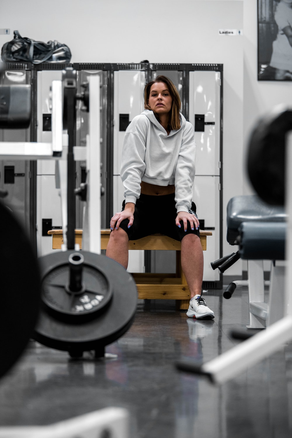 man in white long sleeve shirt and black shorts sitting on black and gray exercise bench