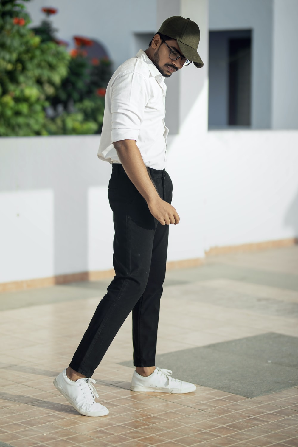 man in white t-shirt and black pants standing on white floor
