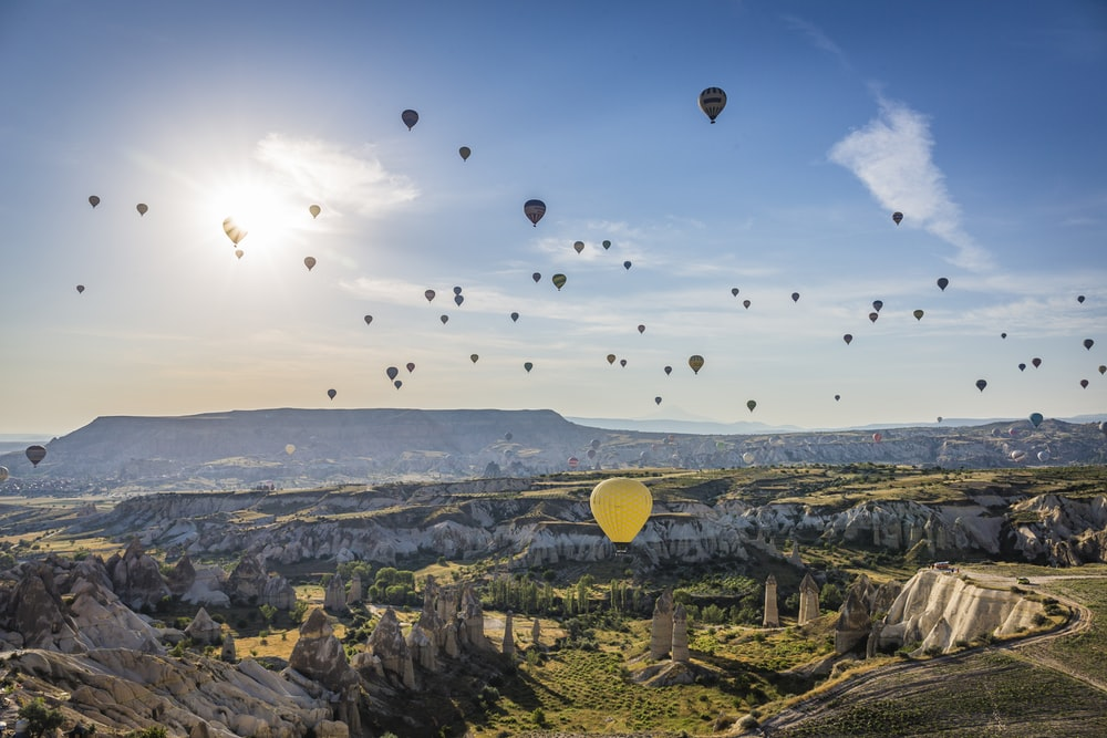hot air balloons flying over city during daytime