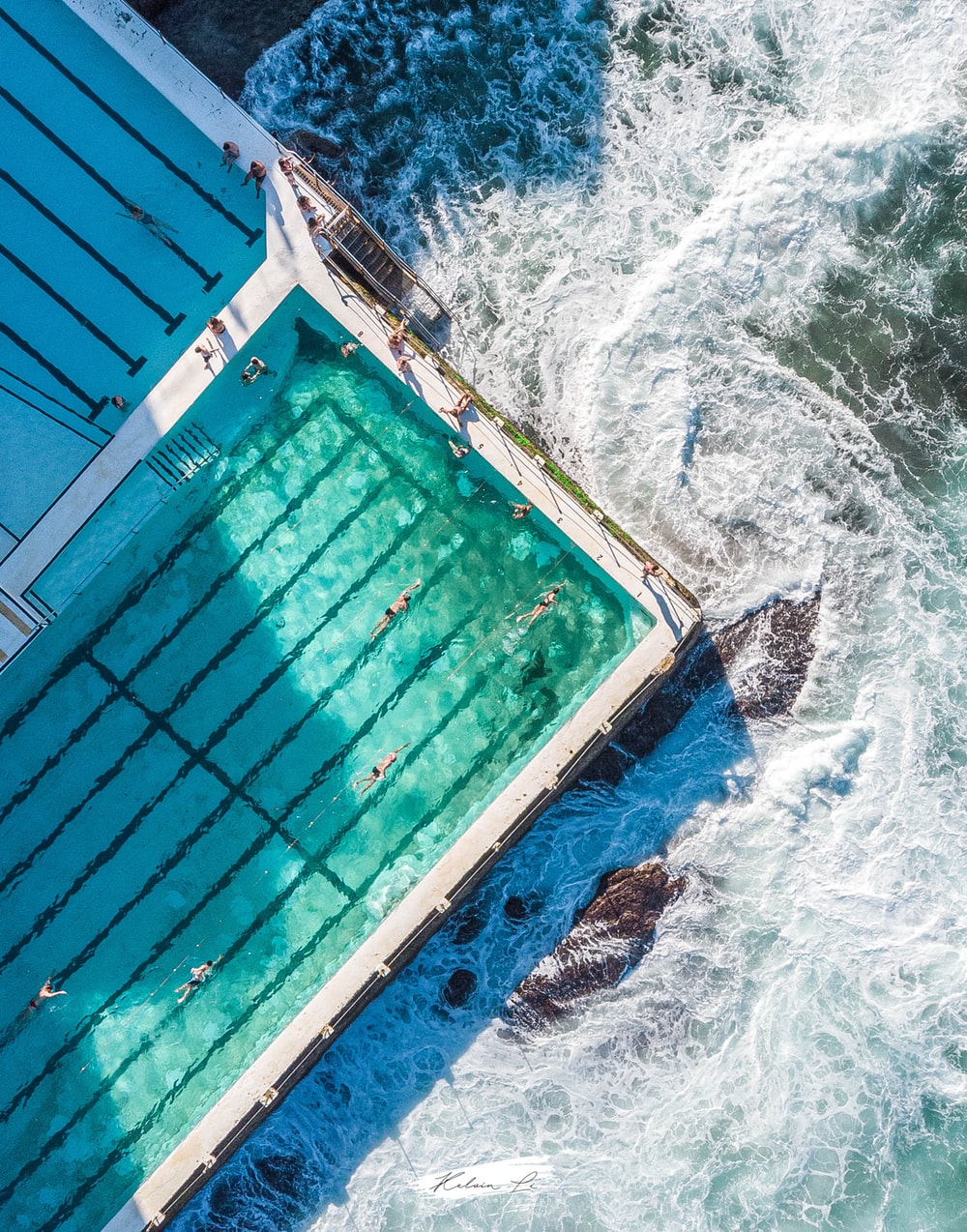 blue and brown swimming pool beside blue and white ocean water during daytime
