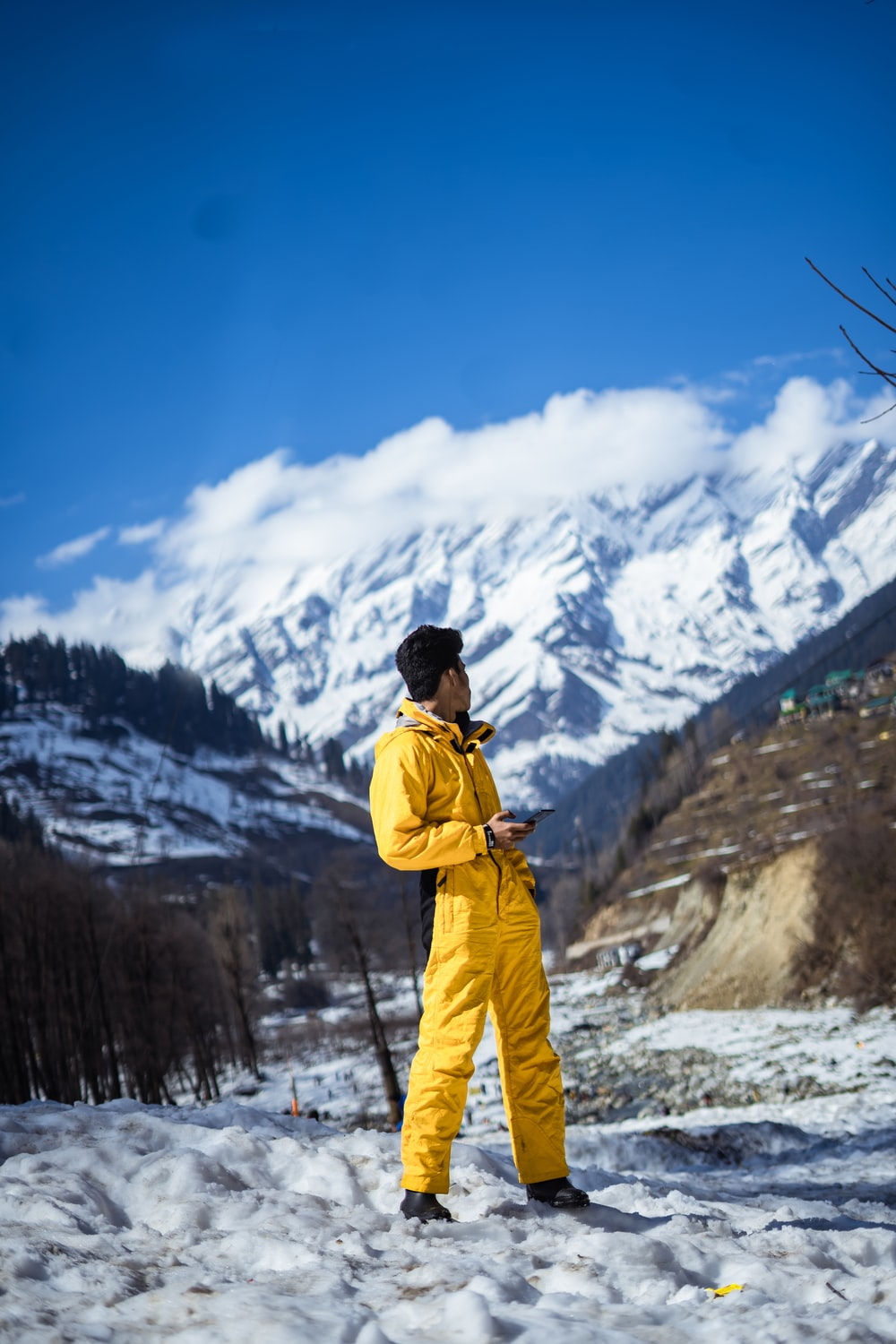 man in yellow jacket and blue pants standing on snow covered ground during daytime