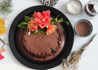 chocolate cake with pink flower on black ceramic plate
