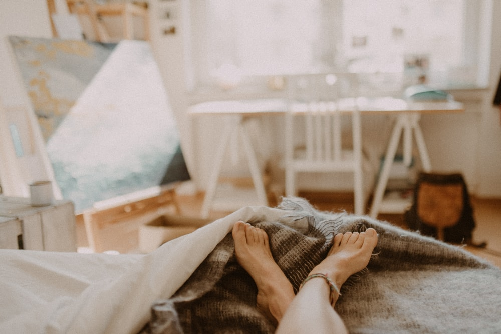 person lying on bed covered with blanket