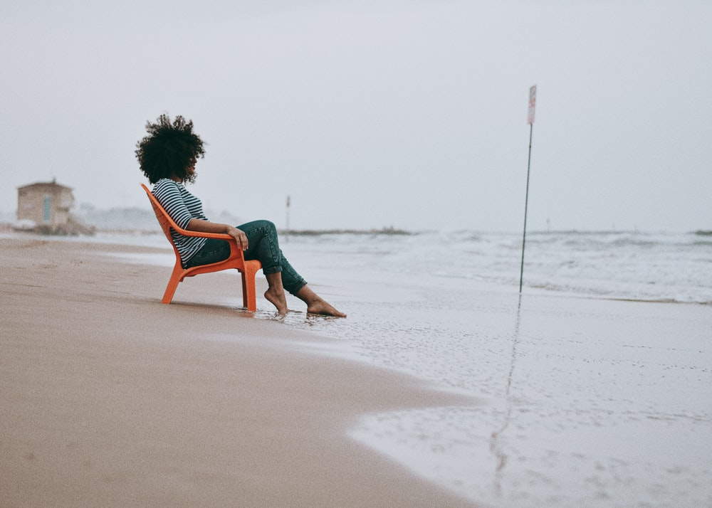 woman in green dress sitting on brown wooden chair on beach during daytime