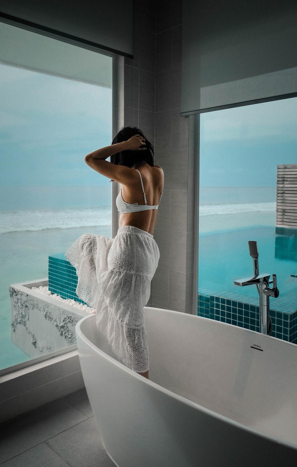 woman in white brassiere and blue denim jeans sitting on white ceramic bathtub