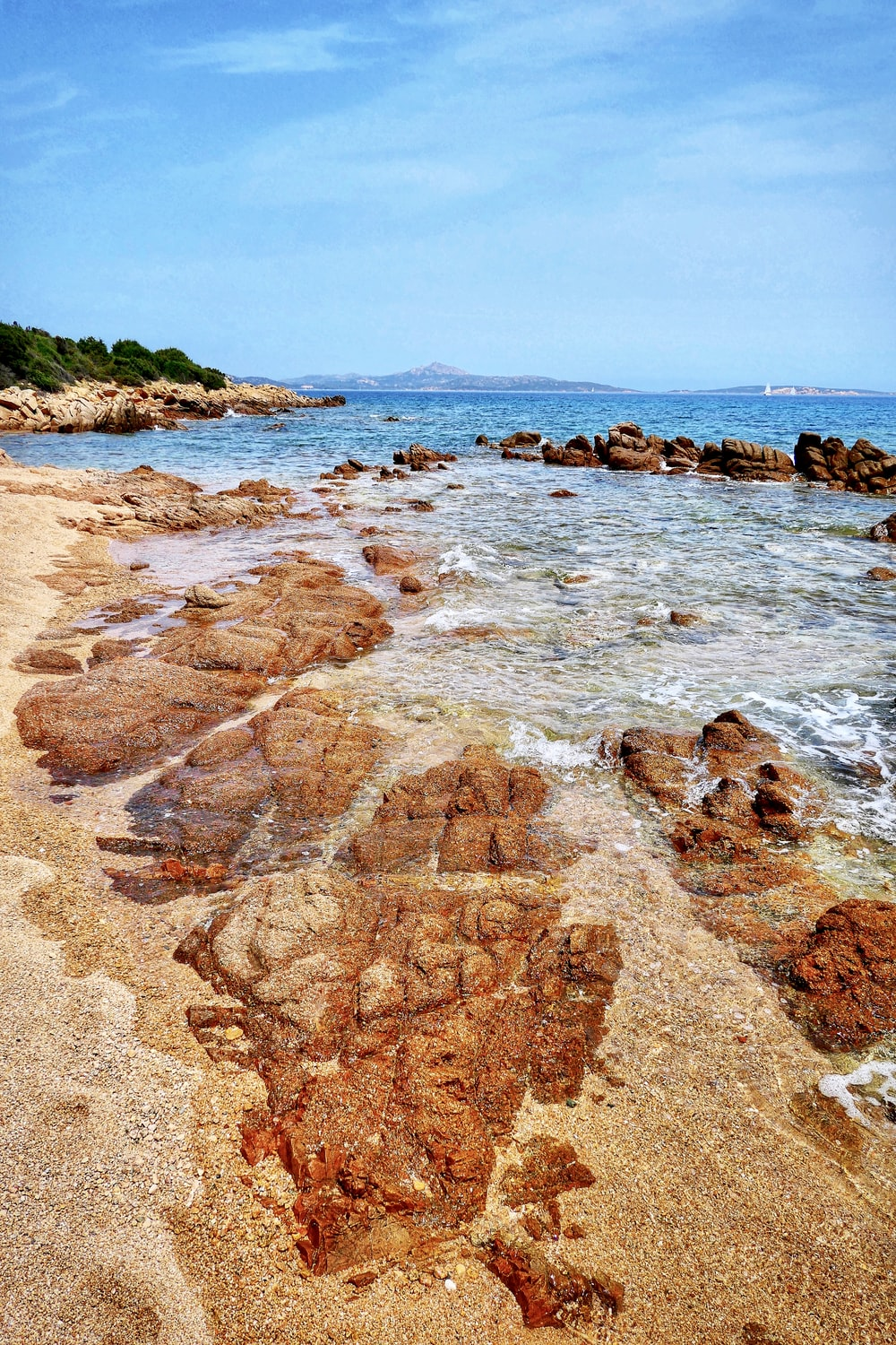 brown rocky shore near green mountain under blue sky during daytime