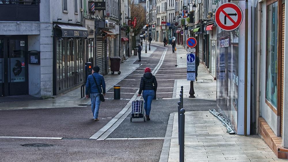 man in blue jacket and blue denim jeans walking on sidewalk during daytime