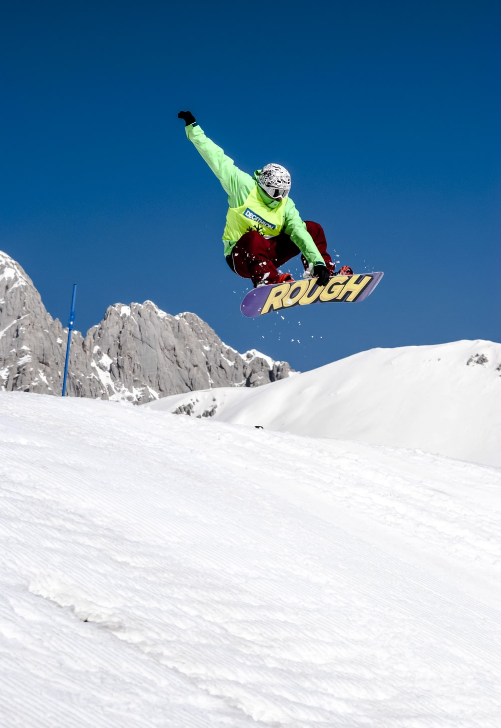 man in green jacket riding snowboard on snow covered mountain during daytime