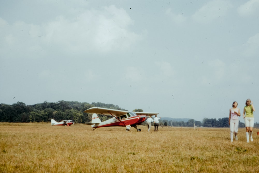 white and red plane on green grass field under white clouds during daytime