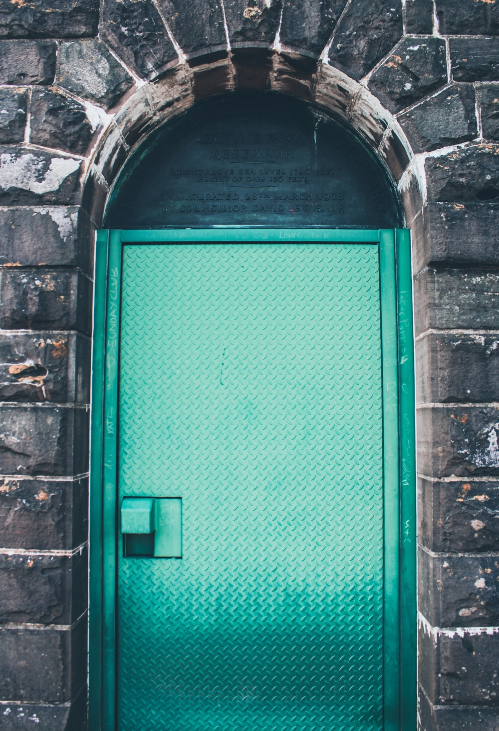 green wooden door on brick wall