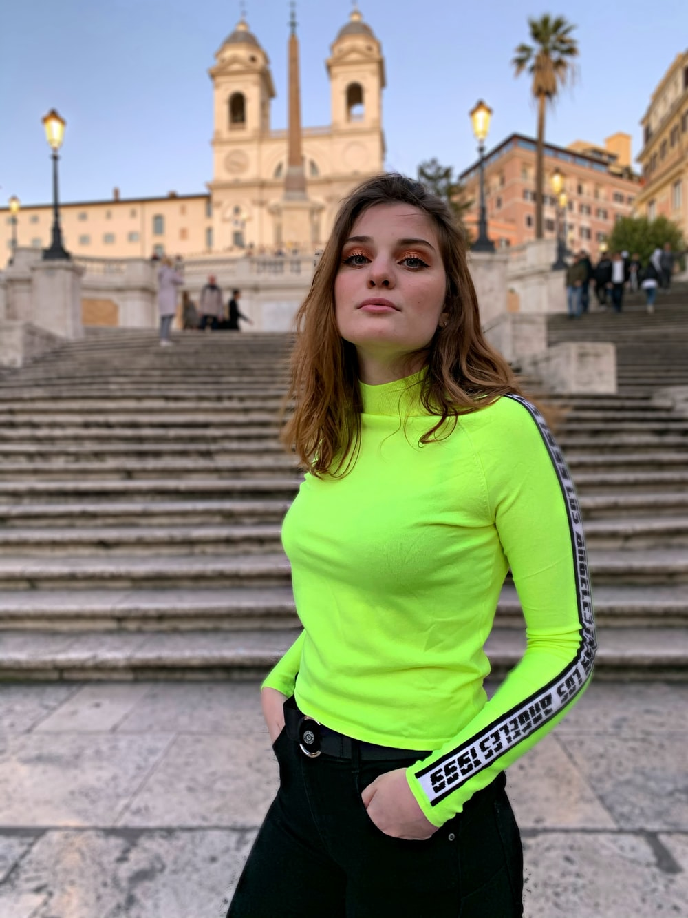 woman in green long sleeve shirt and black pants standing on stairs