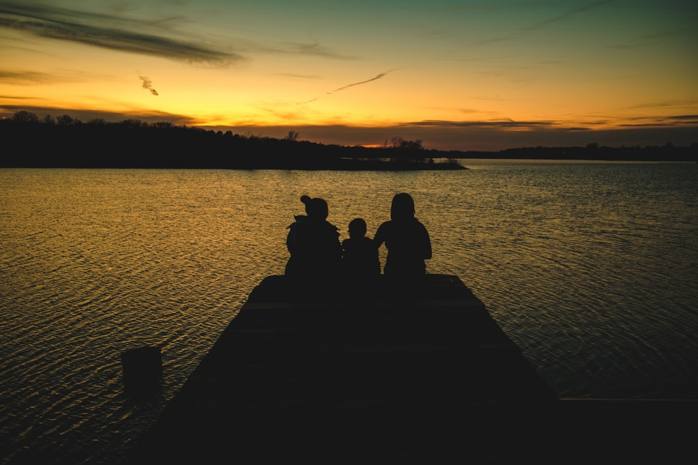 silhouette of 2 people sitting on dock during sunset