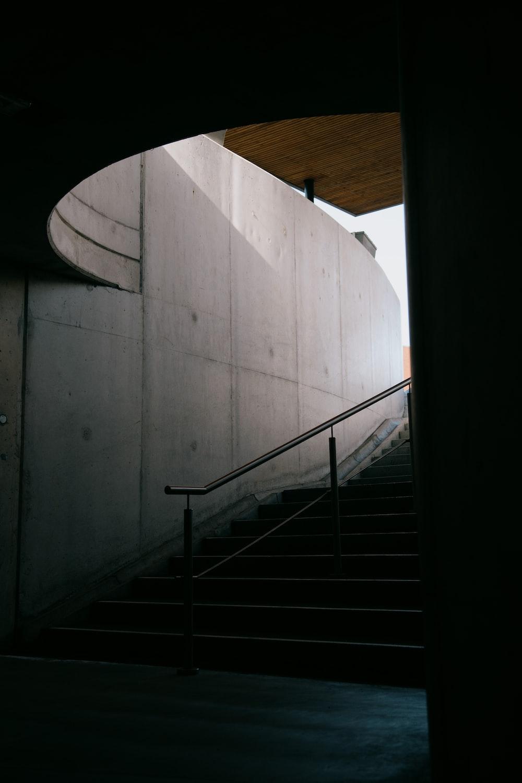 black metal staircase on white concrete wall