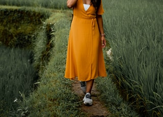 woman in orange dress standing on green grass field during daytime