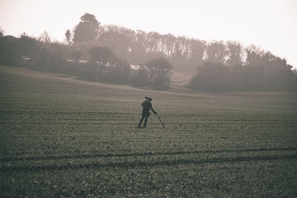man in black jacket walking on green grass field during daytime