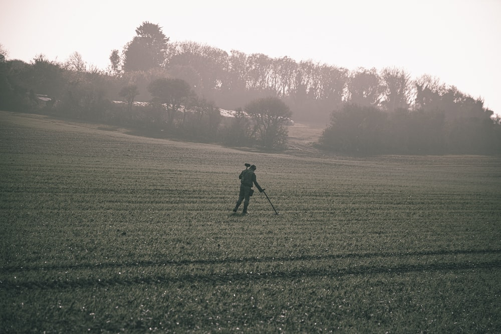 man in black jacket walking on green grass field during daytime
