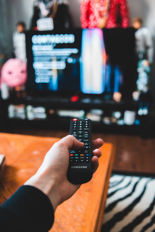 person holding black remote control