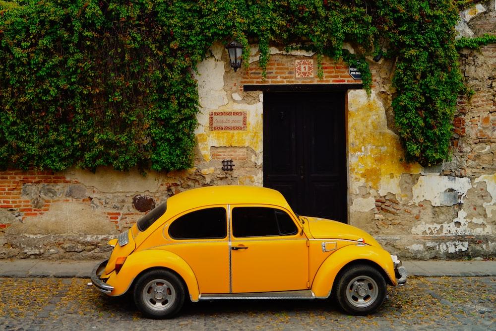 yellow volkswagen beetle parked beside brown brick wall