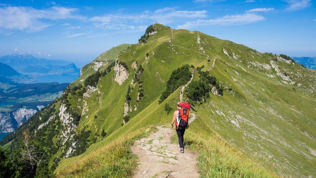 woman with baby on her back hiking an adventerous path on top of a mountain
