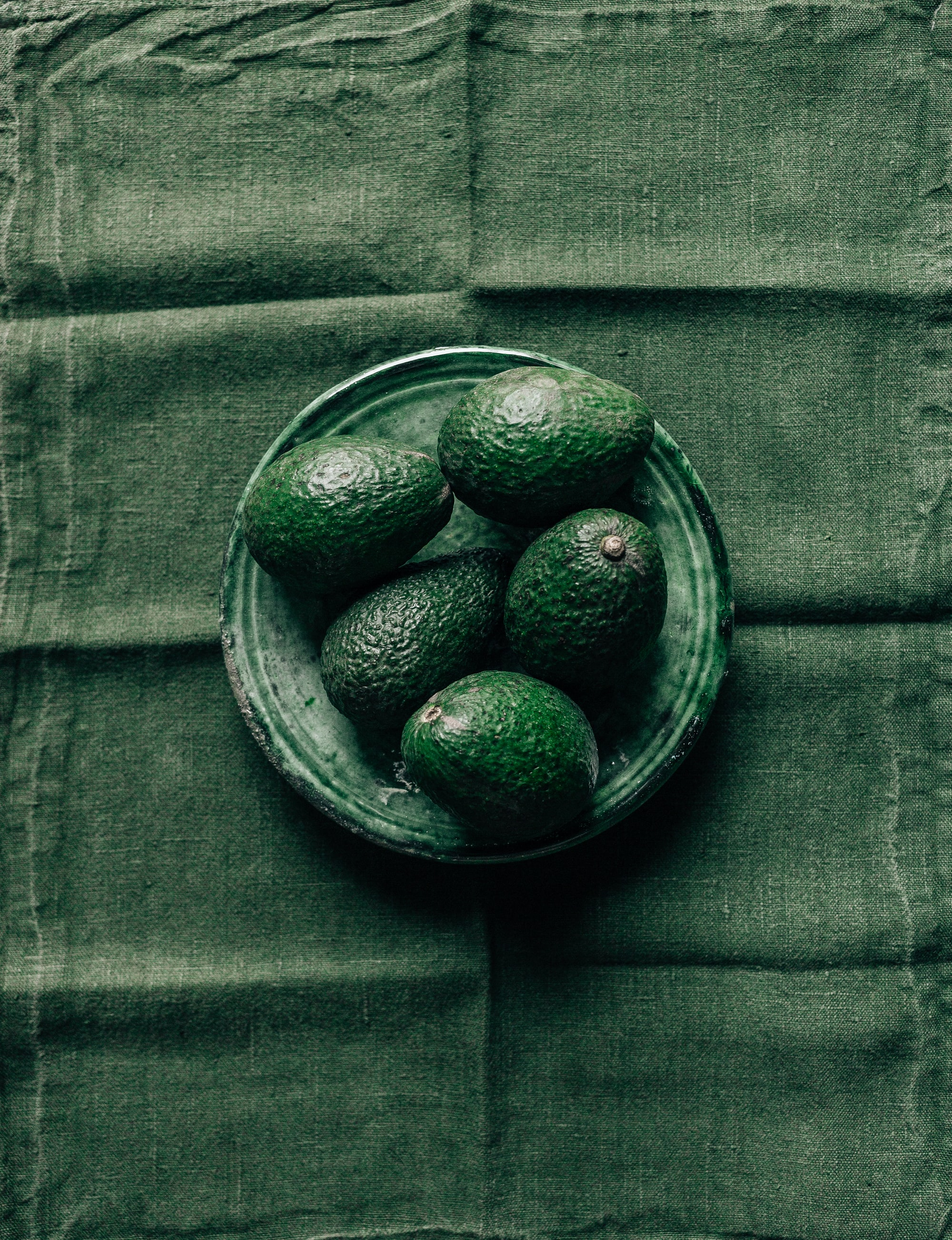 Avocados against Moroccan pottery and Japanese linens.