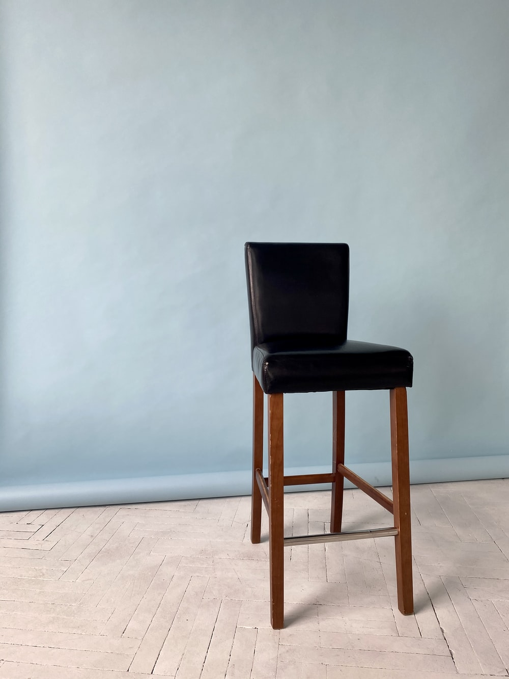 brown wooden chair beside white wall