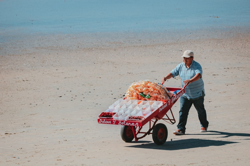 man in white dress shirt and blue denim jeans pushing red and white cart on beach