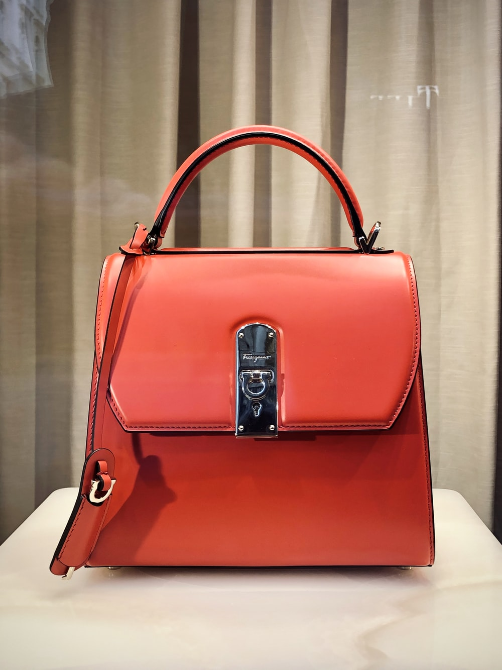 red leather handbag on white table