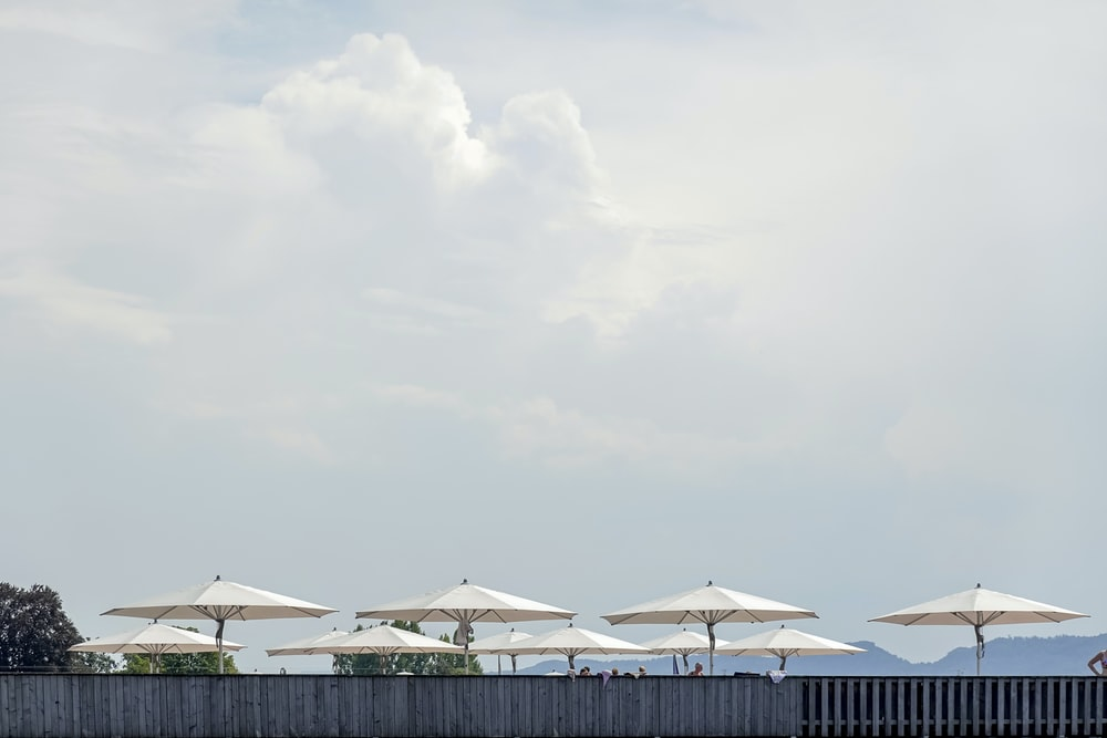 white and green patio umbrellas on beach during daytime
