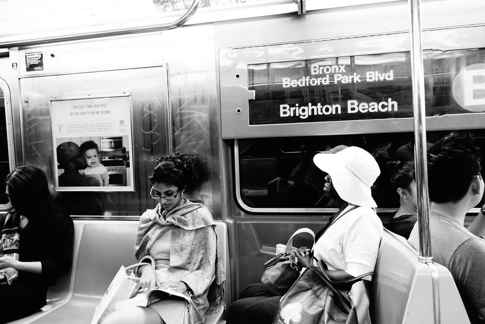 woman in white coat sitting on train seat