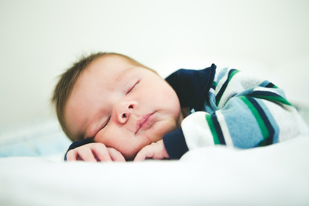 baby in black and white stripe shirt lying on bed