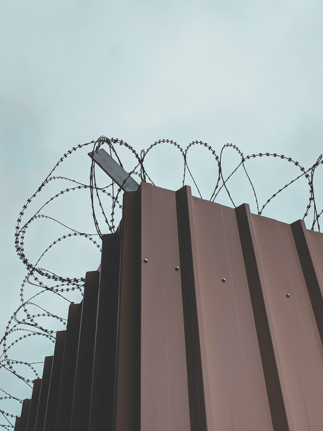 Barbed Wire and metal sheet wall to protect a dangerous construction site.