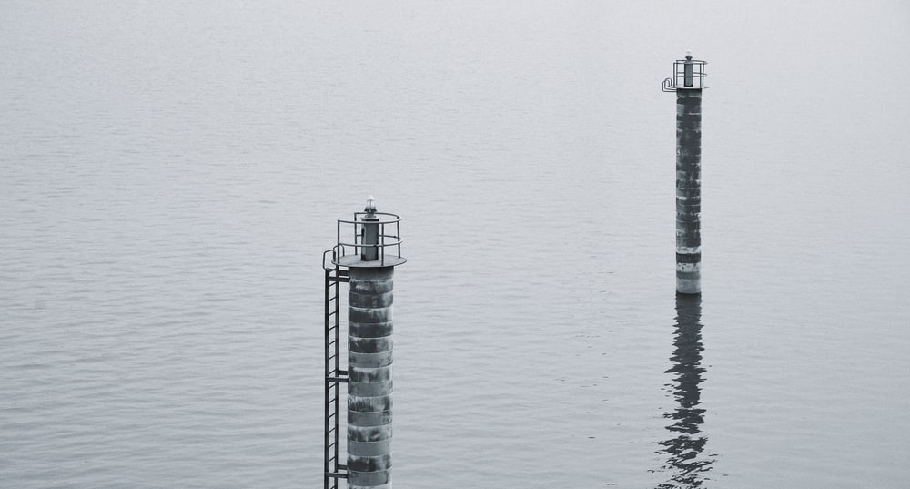 white and black lighthouse on body of water during daytime