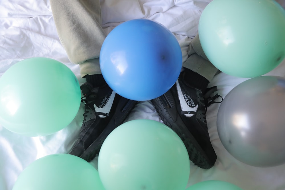blue and green balloons on black and white textile