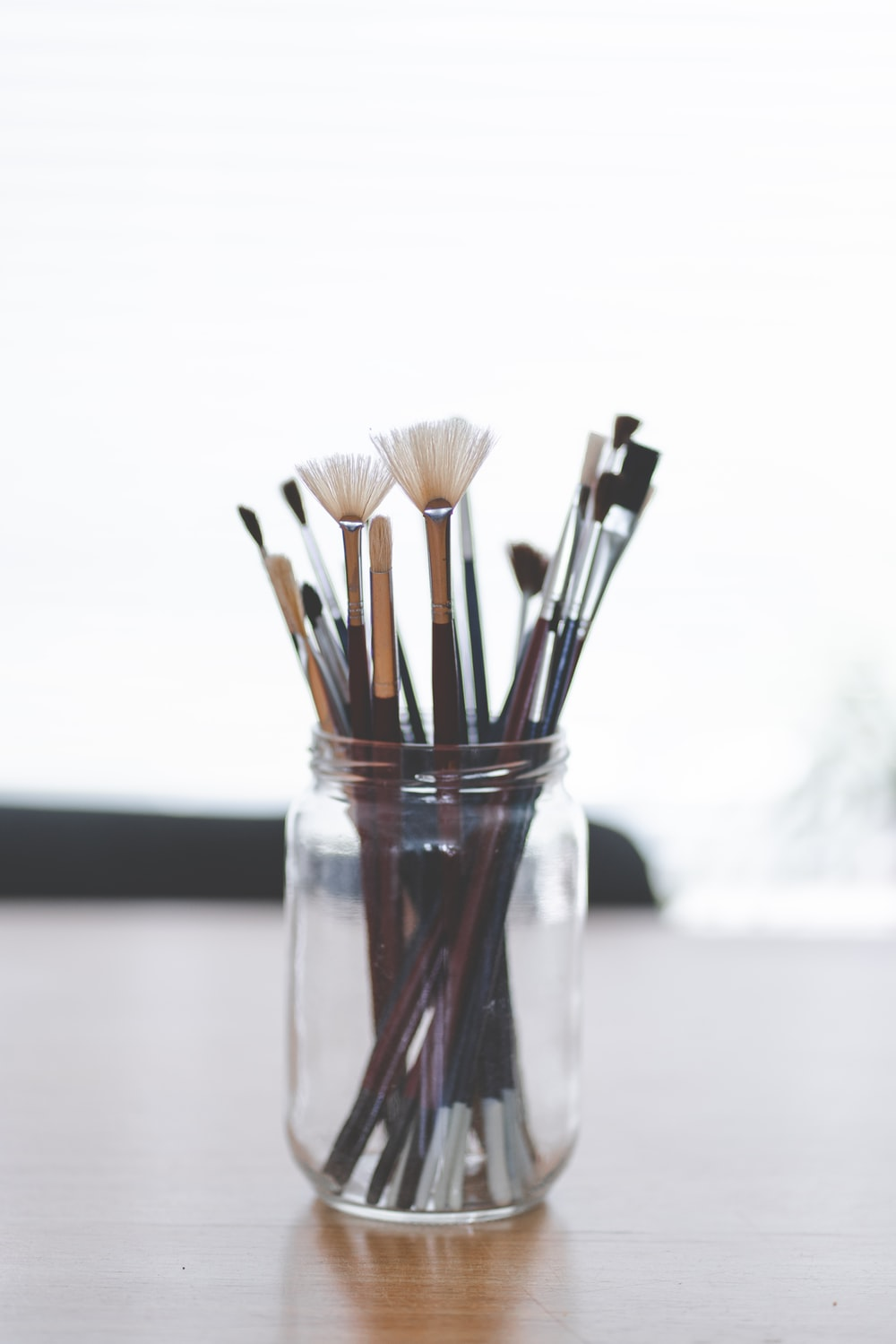 brown and black makeup brush set in clear glass jar