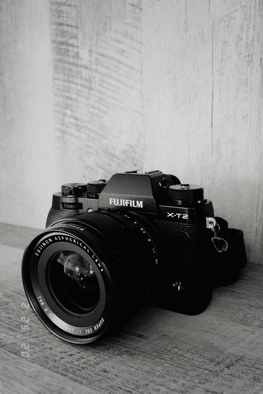 black nikon dslr camera on white textile