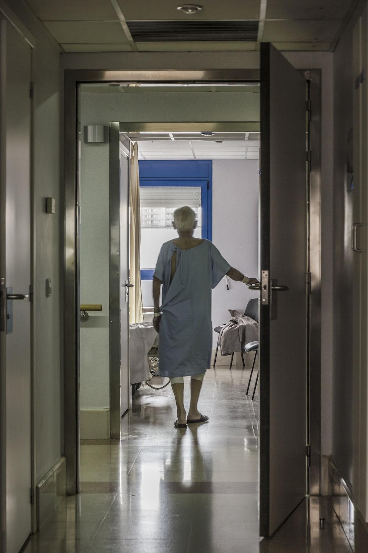 man in blue scrub suit standing near brown wooden door