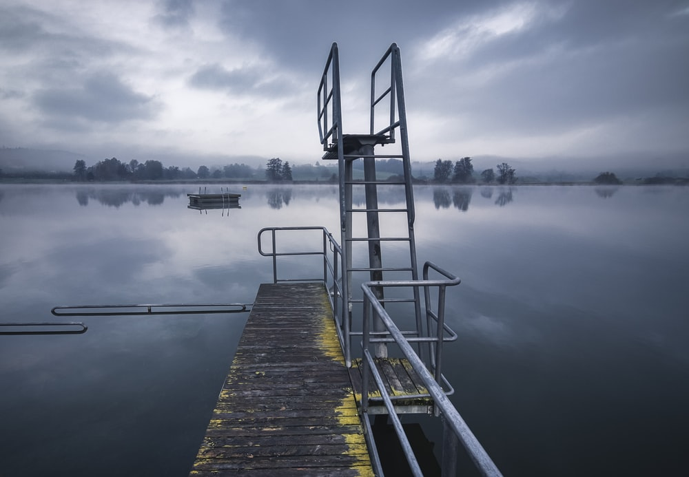 brown wooden dock on lake under cloudy sky during daytime