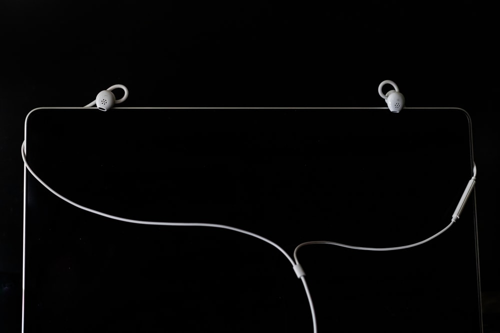 white earbuds on black surface