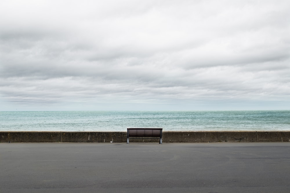 brown wooden bench on gray concrete floor near sea under white clouds during daytime