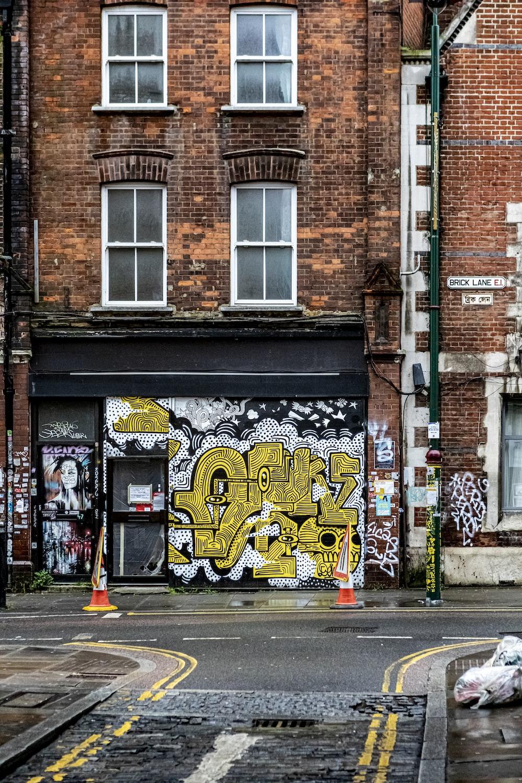 brown brick building with graffiti
