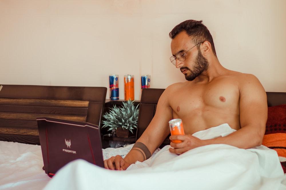 topless man holding orange plastic bottle sitting on bed