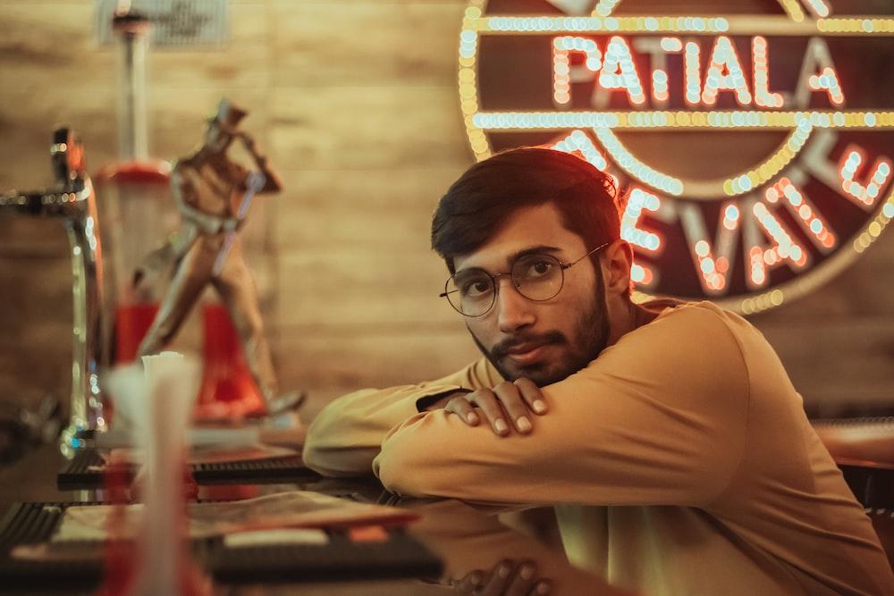man in brown long sleeve shirt wearing black framed eyeglasses