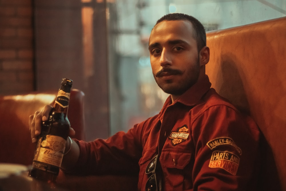 man in red and black zip up jacket holding beer bottle