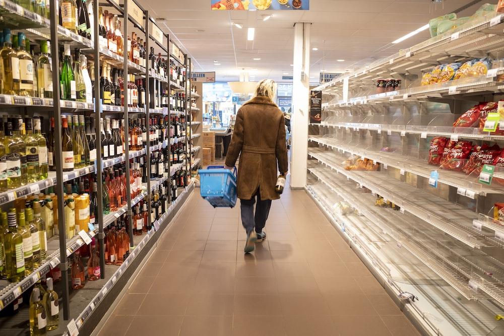 woman in brown coat walking on hallway